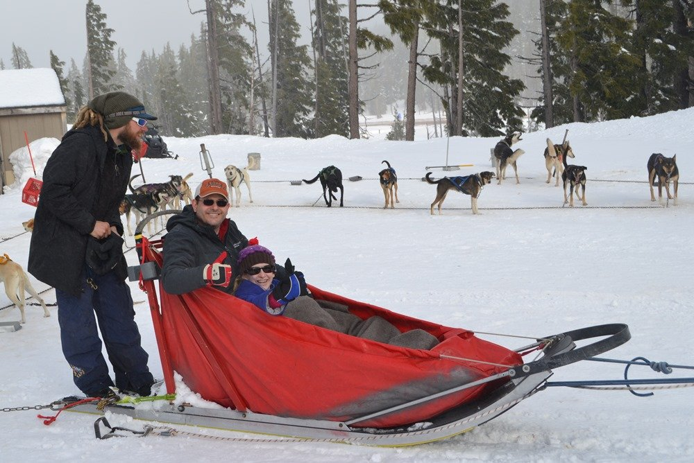 """Snuggled in the """"basket"""" of a sled, Mike and Bethy VanCleave get ready to mush at Mount Bachelor in Central Oregon."""